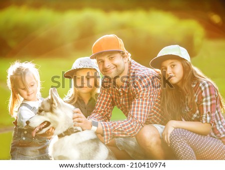 Father and his two daughters in park with dog Husky spend fun time. - stock photo