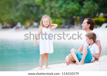 Father and his two kids sitting on a white sand beach