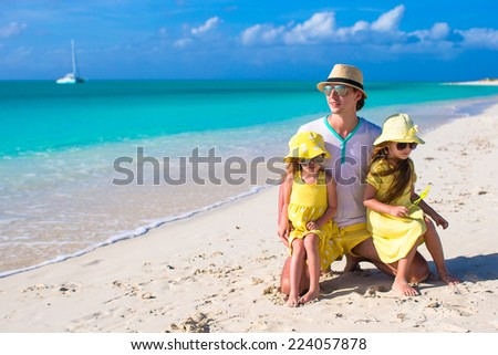 Father and his two kids walking by the sea - stock photo