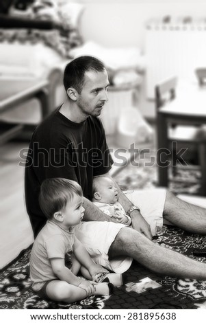 Father and his two sons, watching TV in the living room, black and white conversion - stock photo