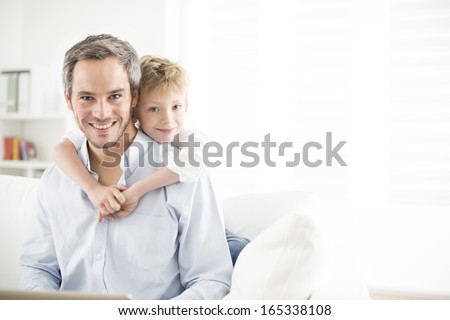 Father and his young son smiling and look the camera - stock photo