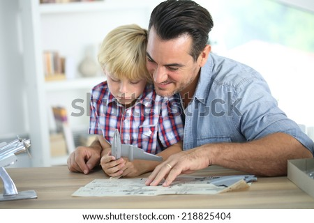 Father and kid making a plane model - stock photo