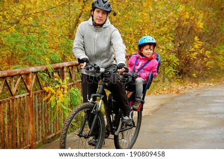 Father and kid on bike, cycling in autumn park