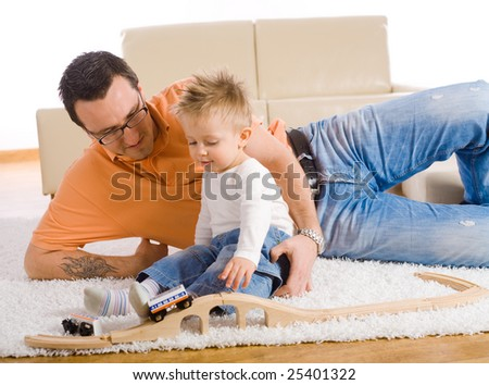 Father and kid playing together on floor of livingroom, smiling. - stock photo