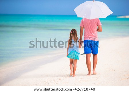 Father and kid walking on white sandy beach - stock photo