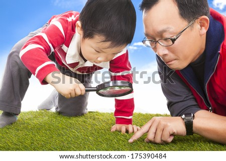 father and kid with magnifying glass to discover - stock photo