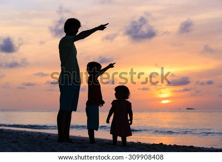 father and kids at sunset beach, pointing at the sun