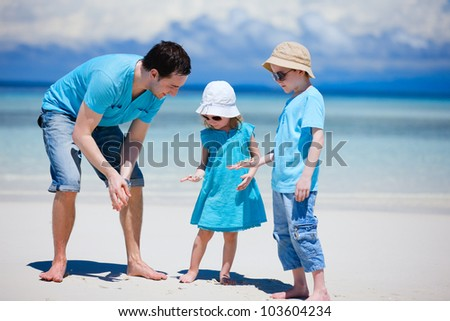 Father and kids at tropical beach holding starfish