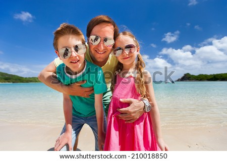 Father and kids at tropical beach vacation having fun outdoors - stock photo