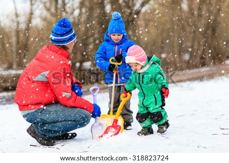father and kids digging snow in winter park, family winter fun - stock photo