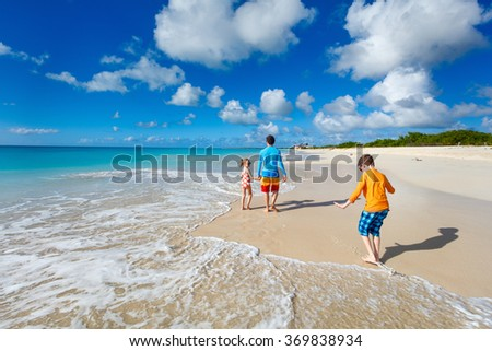 Father and kids enjoying Caribbean beach vacation on tropical island - stock photo