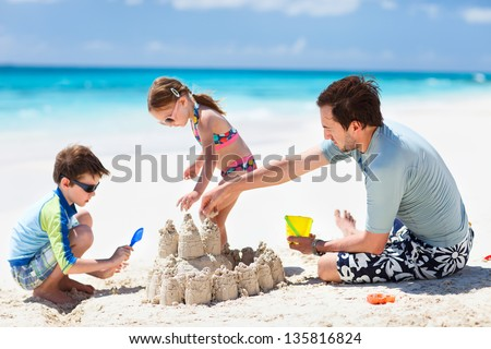 Father and kids making sand castle at tropical beach - stock photo
