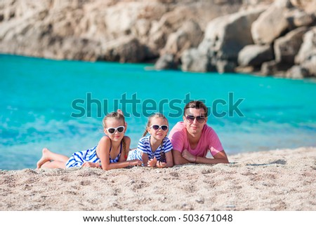 Father and kids on white sandy beach