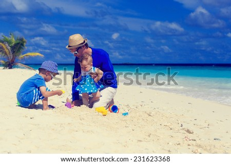 Father and kids playing at tropical sand beach - stock photo