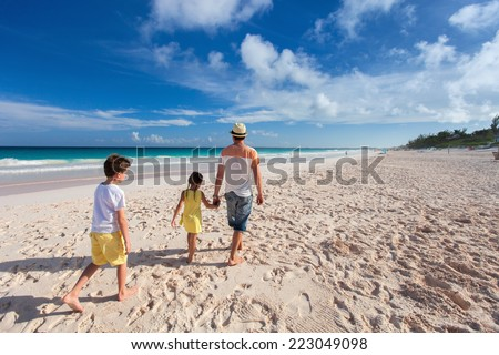 Father and kids walking along tropical beach on Bahamas