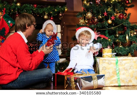 father and kids with presents in christmas home