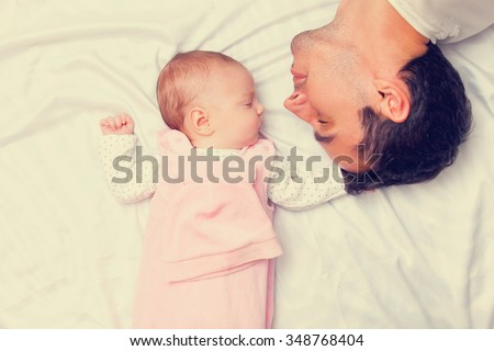 Father and little baby in the bad  - stock photo