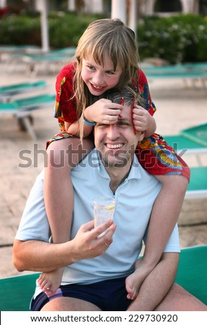 father and little blond daughter after swimming beside the pool in beach resort - stock photo