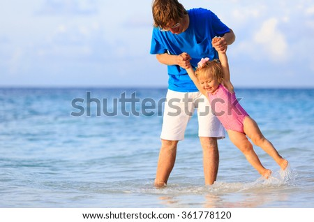 father and little daughter having fun on beach - stock photo