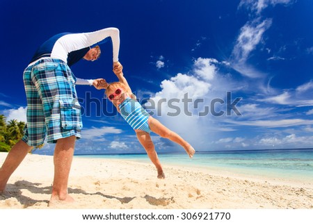 father and little daughter having fun on summer beach vacation - stock photo