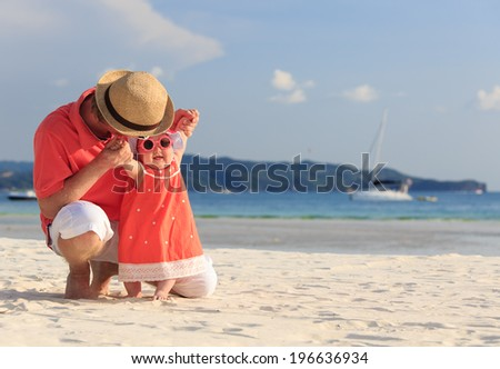 father and little daughter having fun on the beach