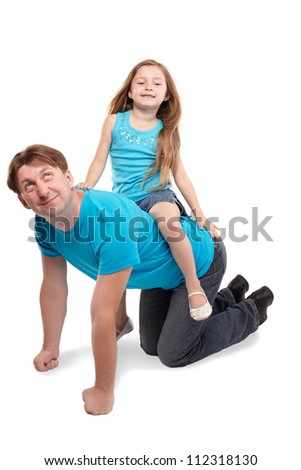 Father and little daughter in blue t-shirts play horse-ride - stock photo