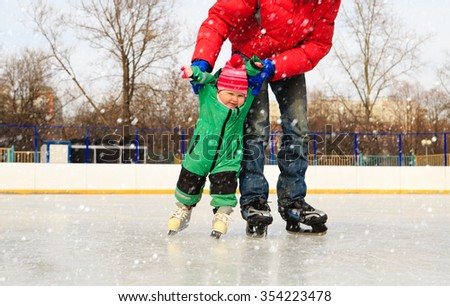 father and little daughter learning to skate in winter snow - stock photo