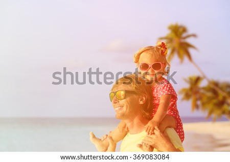 father and little daughter on summer beach - stock photo