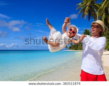 father and little daughter play at beach - stock photo