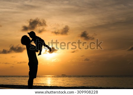 Father and little daughter play silhouettes on beach at sunset
