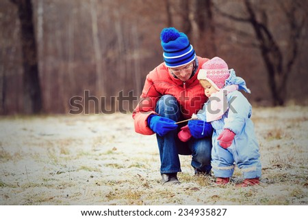 father and little daughter playing in winter park