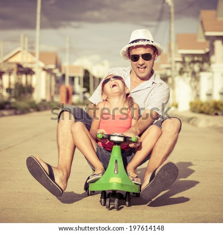 father and little daughter playing near a house at the day time - stock photo