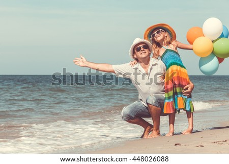 Father and little daughter playing with balloons on the beach at the day time. People having fun on the nature. Concept of friendly family. - stock photo