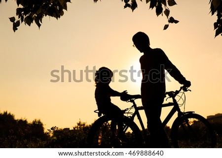 father and little daughter riding bike at sunset