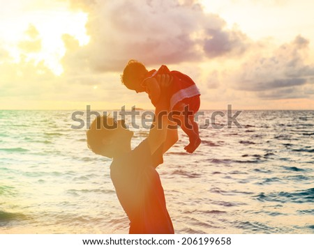 Father and little daughter silhouettes on beach at sunset - stock photo