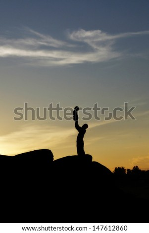 Father and little daughter silhouettes on rock - stock photo