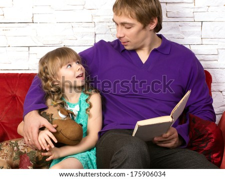 father and little daughter sitting on red sofa with toy and book looking at each other and  communicated  - stock photo