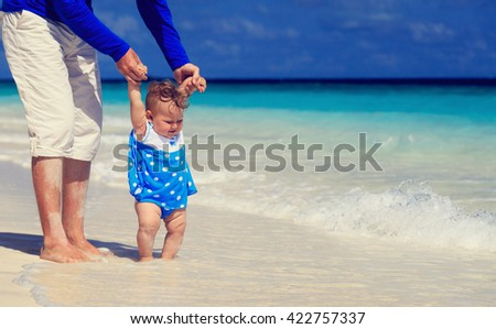 father and little daughter walking on the beach