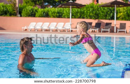 Father and little girl enjoy swimming in the pool - stock photo