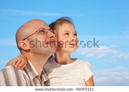 father and little girl on sky background are looking at sky - stock photo