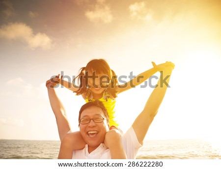 Father and little girl playing on the beach at the sunset - stock photo