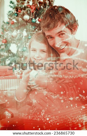Father and little girl playing with Christmas presents against glittering christmas tree design - stock photo
