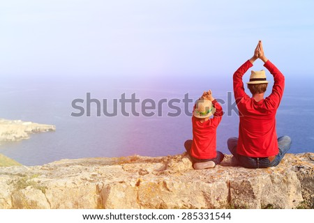 father and little son doing yoga in mountains at the sea - stock photo