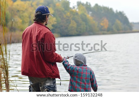 Father and little son fishing together on autumn day outdoors background - stock photo