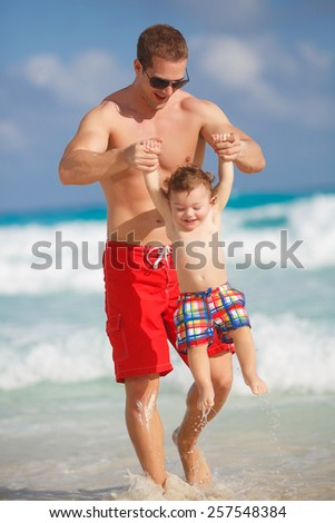 Father and little son having fun on tropical white sand beach near carebbean ocean. Man with little baby boy having fun and playing near the sea water - stock photo