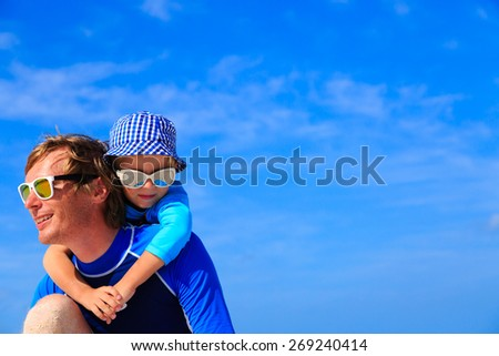 father and little son hug on summer beach, family lifestyle - stock photo