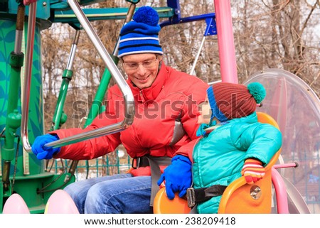 father and little son in amusemement park ride - stock photo