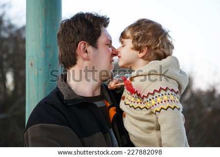 Father and little son in park or forest, outdoors. Hugging and having fun together. - stock photo