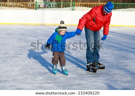 father and little son learning to skate - stock photo