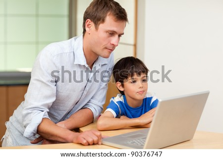 Father and little son looking at laptop